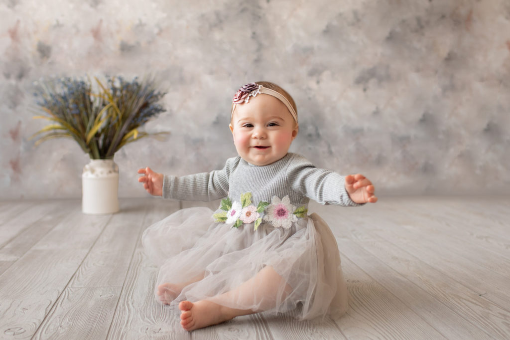baby photo eight month girl Madison dressed in grey floral dress and pink floral headband with arms out to side sitting by herself on grey floor with floral backdrop Gainesville Florida