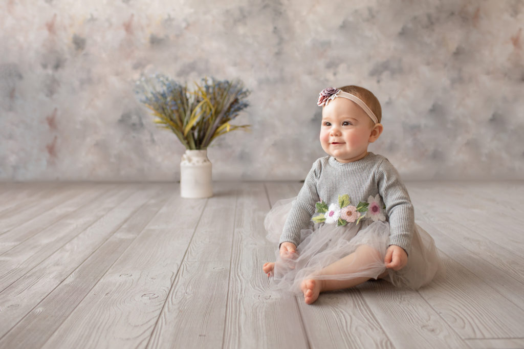 baby photo eight month girl Madison dressed in grey floral dress and pink floral headband sitting by herself looking at her mom on grey floor with floral backdrop Gainesville Florida