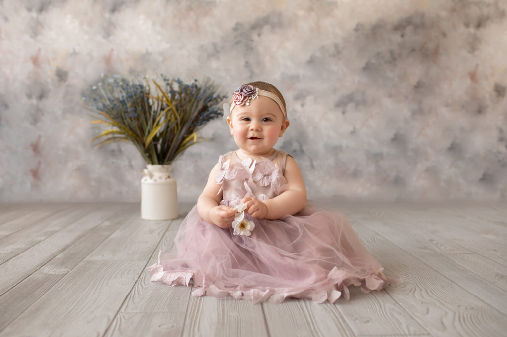 baby photos eight month girl Madison with her best smile dressed in dusty pink floral dress and pink floral headband sitting by herself on grey floor with floral backdrop Gainesville Florida