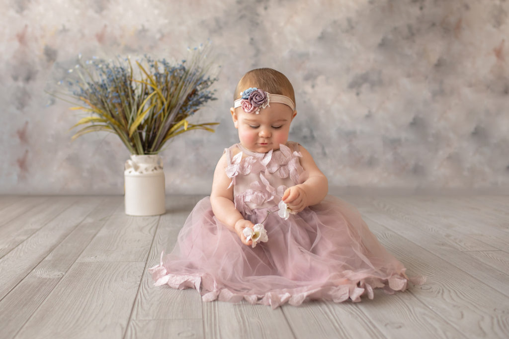 baby photo eight month girl Madison dressed in dusty pink floral dress and pink floral headband sitting by herself on grey floor with floral backdrop playing with flowers in her hands Gainesville Florida