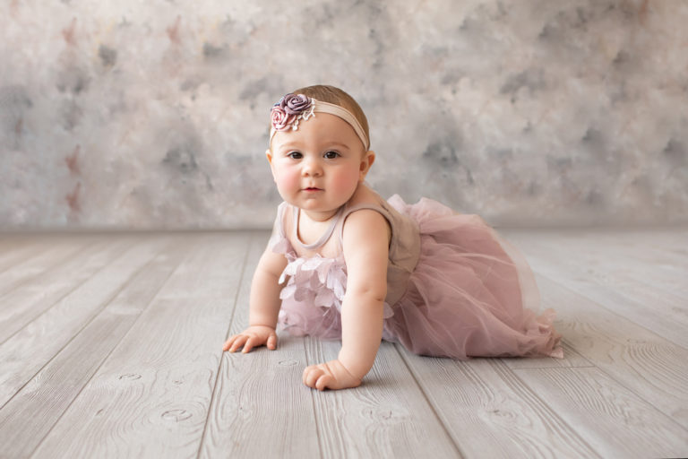 baby photo eight month girl Madison dressed in dusty pink floral dress and pink floral headband crawling on all fours on grey floor with floral backdrop Gainesville Florida