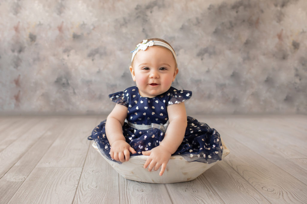 baby photo eight month girl Madison dressed in navy dress with white hearts and white floral headband sitting by herself in white bowl on grey floor with floral backdrop Gainesville Florida