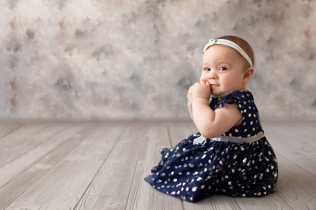baby photo eight month girl Madison dressed in navy dress with white hearts and white floral headband sitting by herself in profile on grey floor with floral backdrop Gainesville Florida