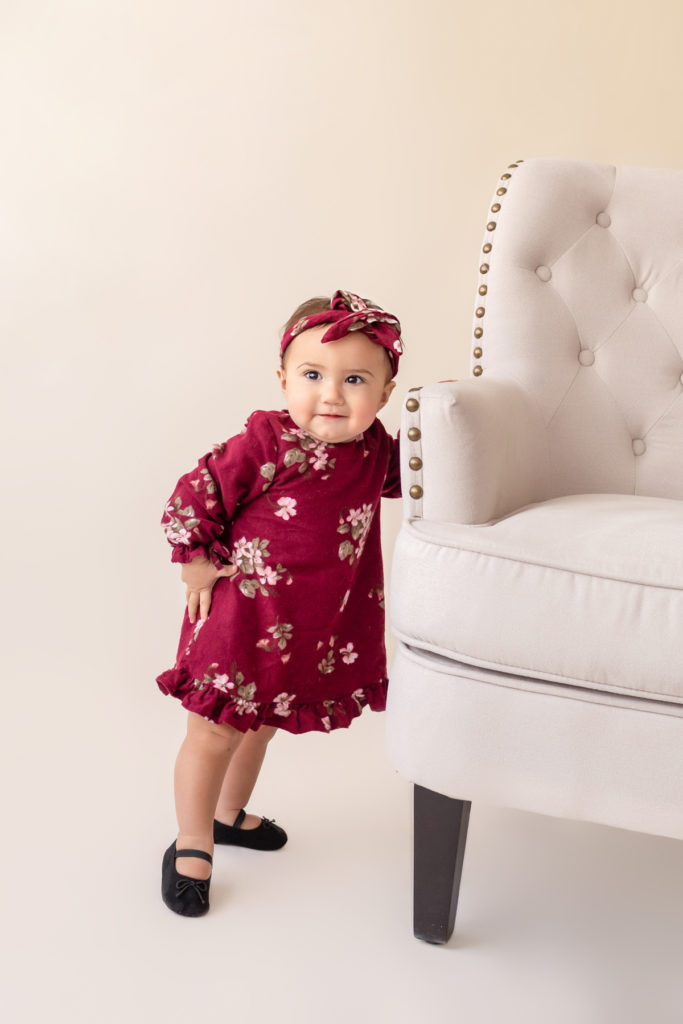 One year twin baby photo girl dressed in burgundy floral dress and headband standing by herself holding onto chair Gainesville Florida