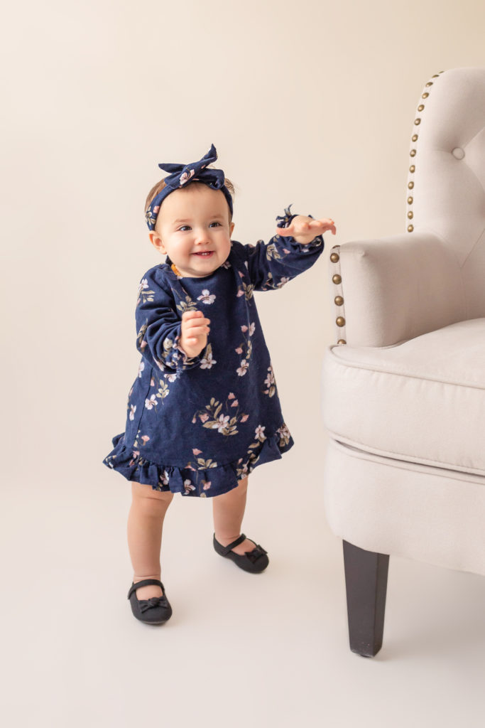 One year twin baby photo girl dressed in navy floral dress and headband standing by herself almost walking first baby steps Gainesville Florida