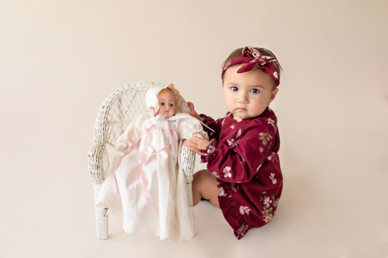 One year twin baby photo girl dressed in burgundy floral dress and headband sitting on cream floor playing with baby doll in wicker chair Gainesville Florida