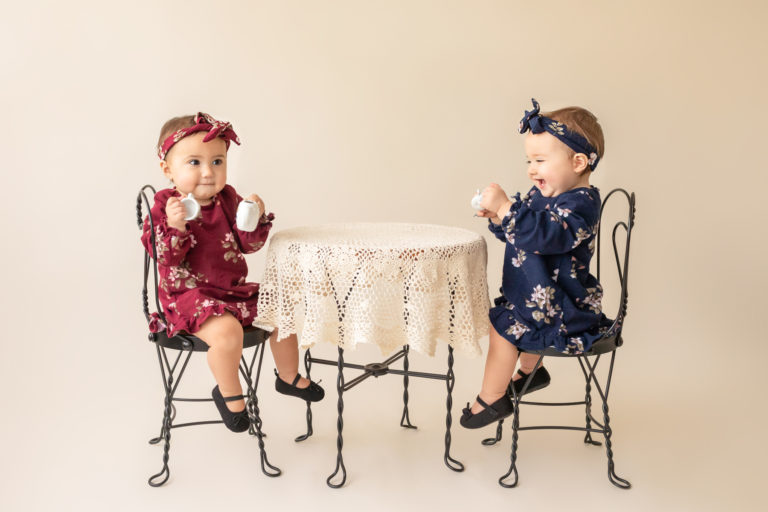 One year twin baby photo girls dressed in burgundy and navy floral dresses and headbands sitting for tea party at lace covered table Gainesville Florida