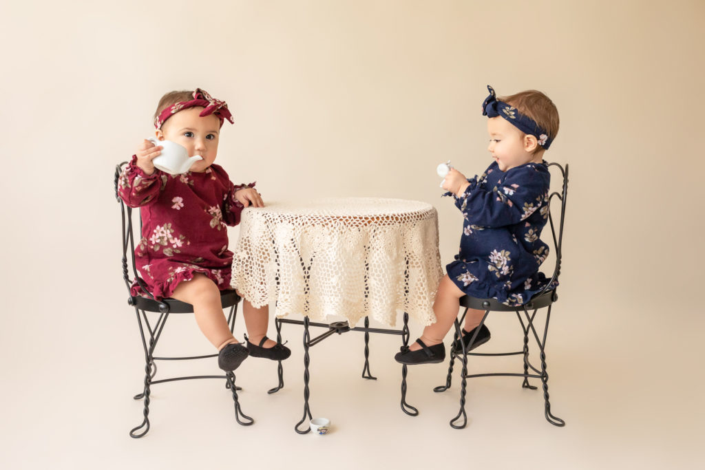 One year twin baby photo girls Renna and Winona dressed in burgundy and navy floral dresses and headbands sitting for tea party at lace covered table Gainesville Florida