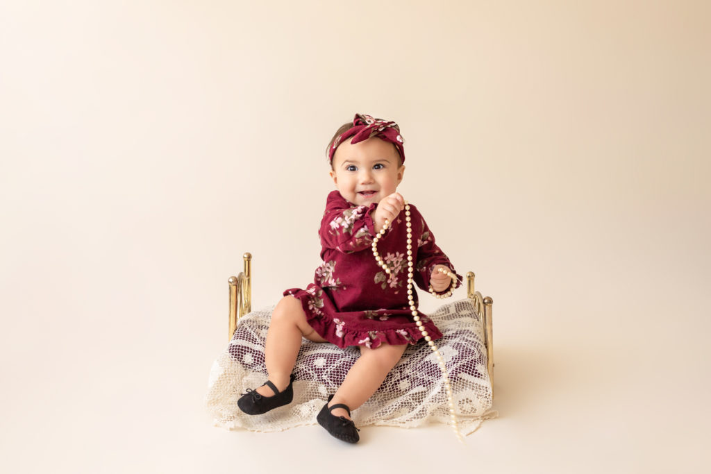 One year twin baby photo girl dressed in burgundy floral dress and headband sitting on lace covered bed playing with strand of pearls Gainesville Florida