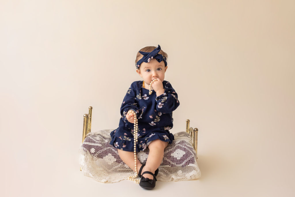 One year twin baby photo girl dressed in navy floral dress and headband sitting on lace covered bed playing with strand of pearls Gainesville Florida