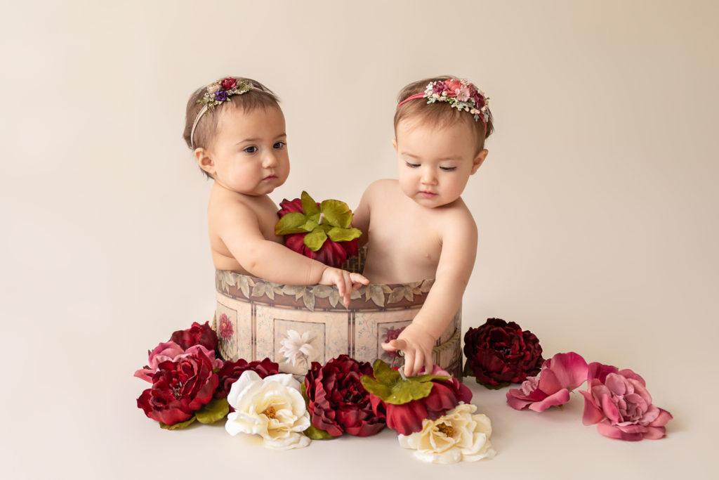 One year twin baby photo girls both naked with floral headbands sitting in same floral hat box playing with burgundy rose and ivory silk flowers Gainesville Florida