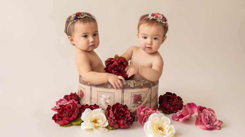 One year twin baby photo girls both naked with floral headbands sitting in same floral hat box playing with burgundy rose and ivory silk flowers looking up Gainesville Florida