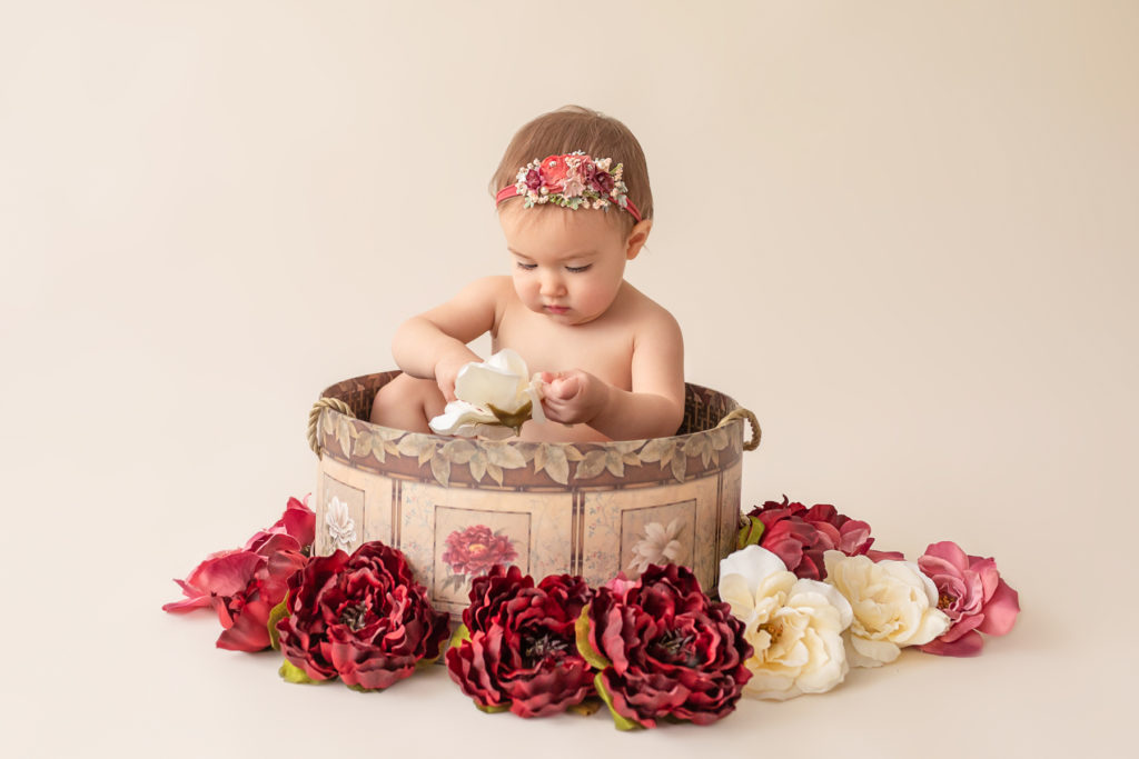 One year twin baby photo girl naked entertained with floral headband sitting in floral hat box playing with burgundy rose and ivory silk flowers Gainesville Florida