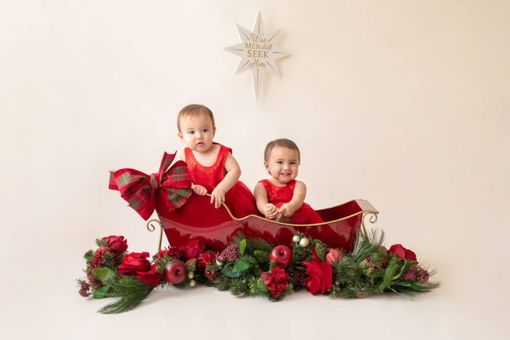 One year twin baby photo girls dressed in red velvet matching dresses sitting in shiny gold trimmed red metal sleigh burgundy and red silk flowers and garland decorations Gainesville Florida