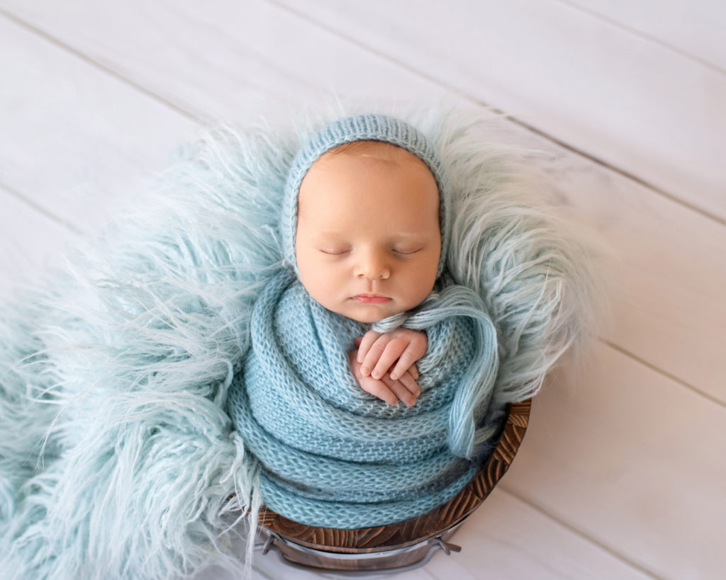 Newborn baby boy Ezra in blue wrap and blue bonnet sound asleep in blue fur stuffed brown bucket Gainesville Florida newborn photographer