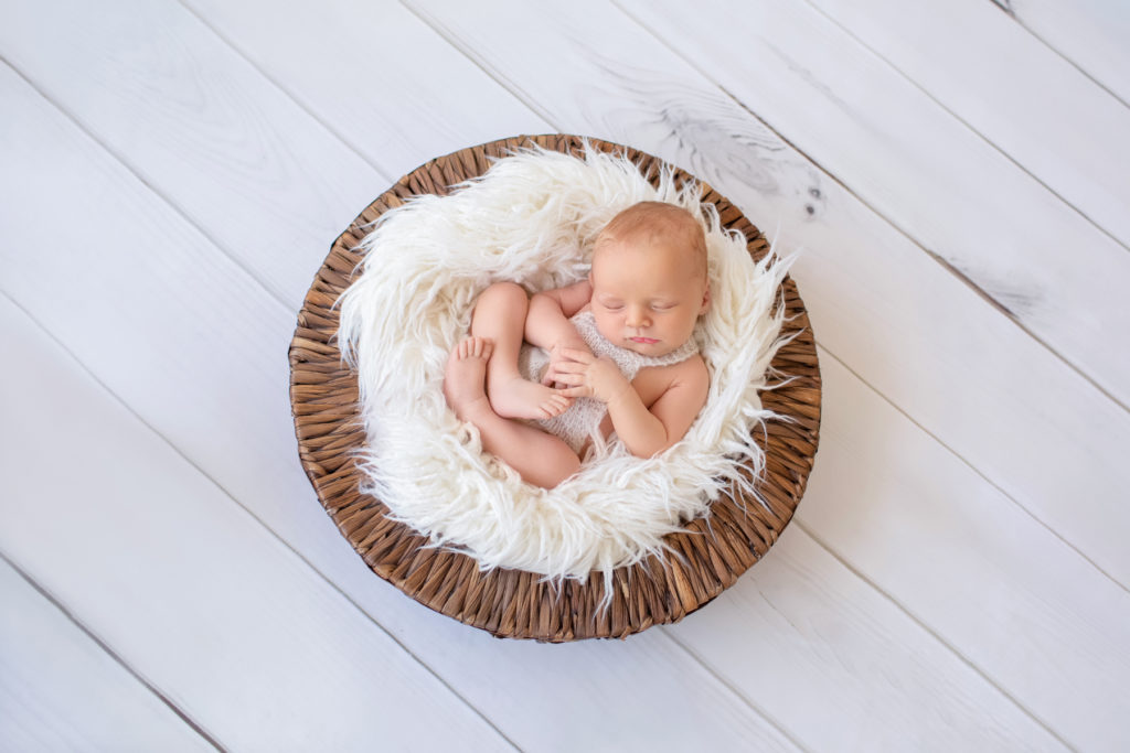 Newborn baby boy Ezra sleeping on white fur in brown basket Gainesville Florida newborn photographer