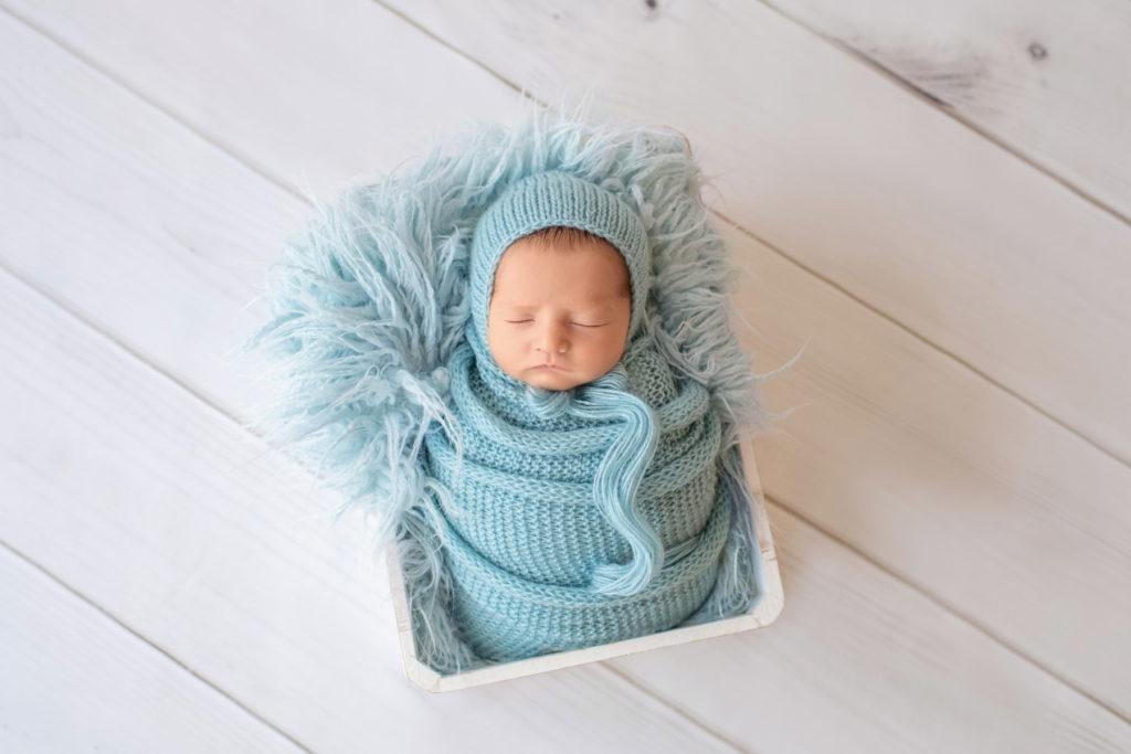 newborn Jeffery in blue handmade knit wrap and matching blue bonnet posed in blue fur stuffed white crate