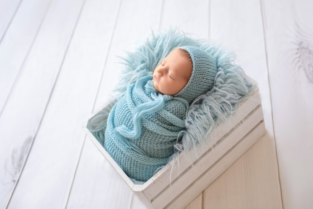 newborn Jeffery in blue handmade knit wrap and matching blue bonnet posed in blue fur stuffed white crate against backlight