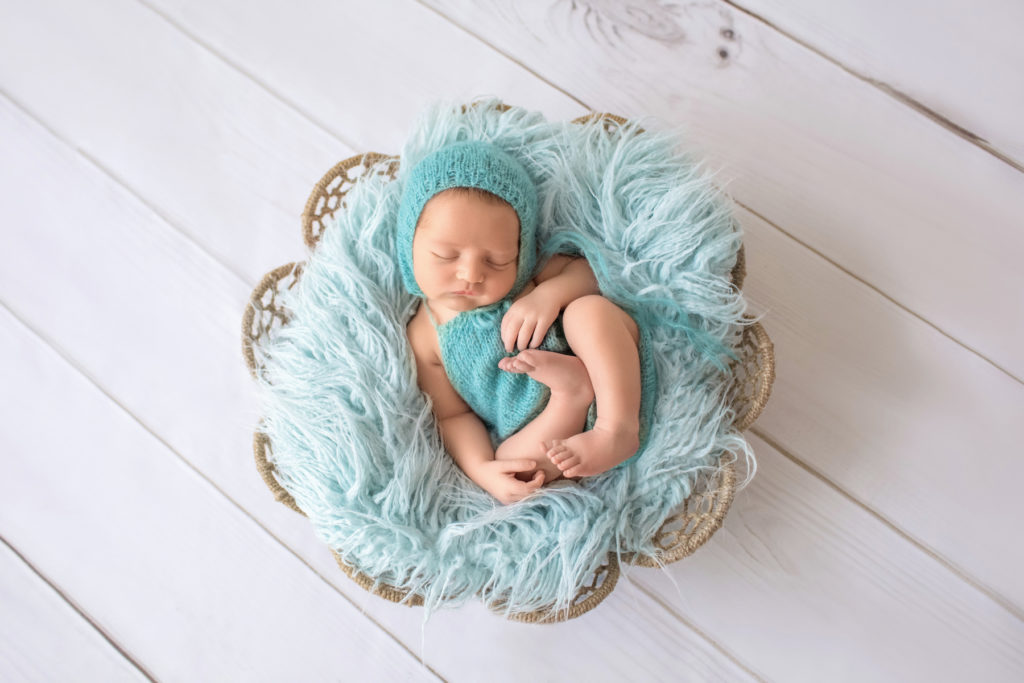 Newborn boy Jeffery dressed in aqua romper and matching aqua romper asleep posed on his back with arms and legs curled tight in fur stuffed brown basket newborn photographer Gainesville Florida