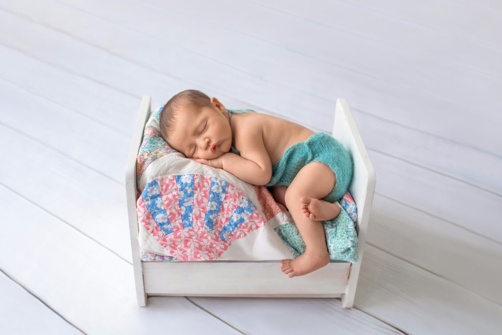 Newborn boy Jeffery outfitted in aqua romper asleep with chin resting on his hand lying on his side on charming quilt covered white wooden bed newborn photographer Gainesville Florida