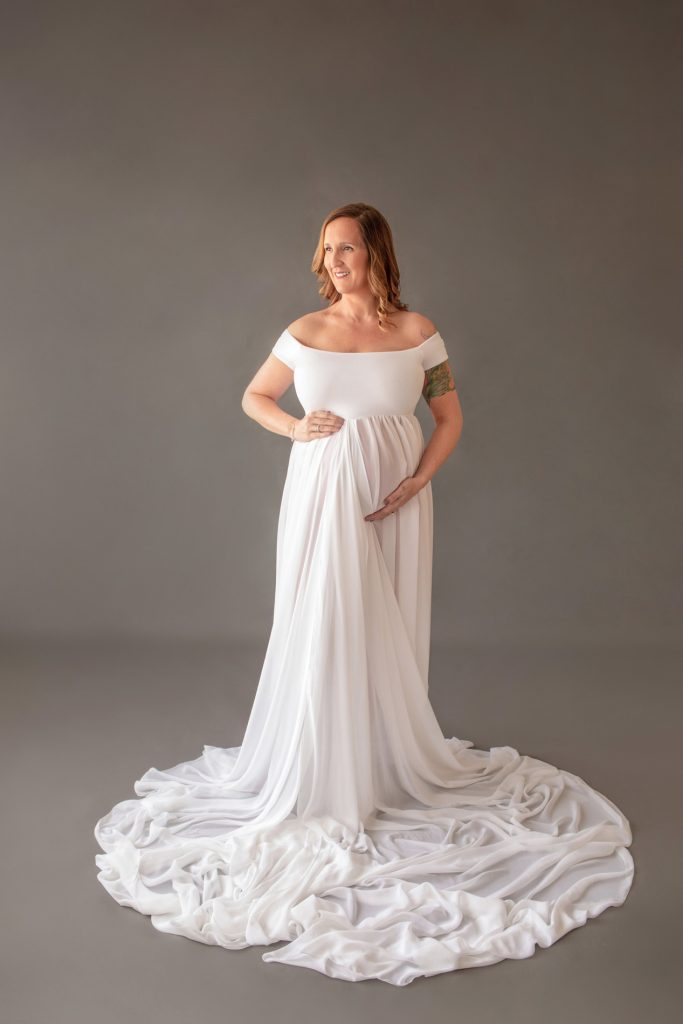 Beautiful pregnant mom in white chiffon maternity gown holding belly and looking sideways on grey background