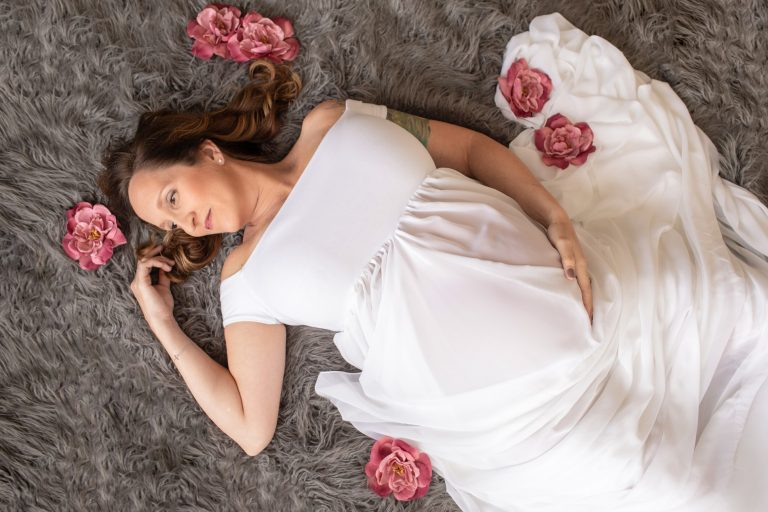 Beautiful pregnant mom to be in white chiffon maternity gown lying on grey fur with dusty rose flowers Gainesville maternity photography