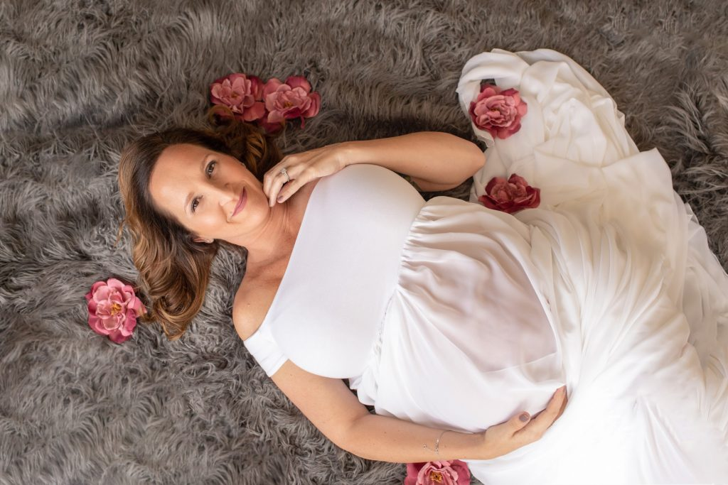 Beautiful pregnant mom to be in white chiffon maternity gown lying on grey fur smiling with dusty rose flowers