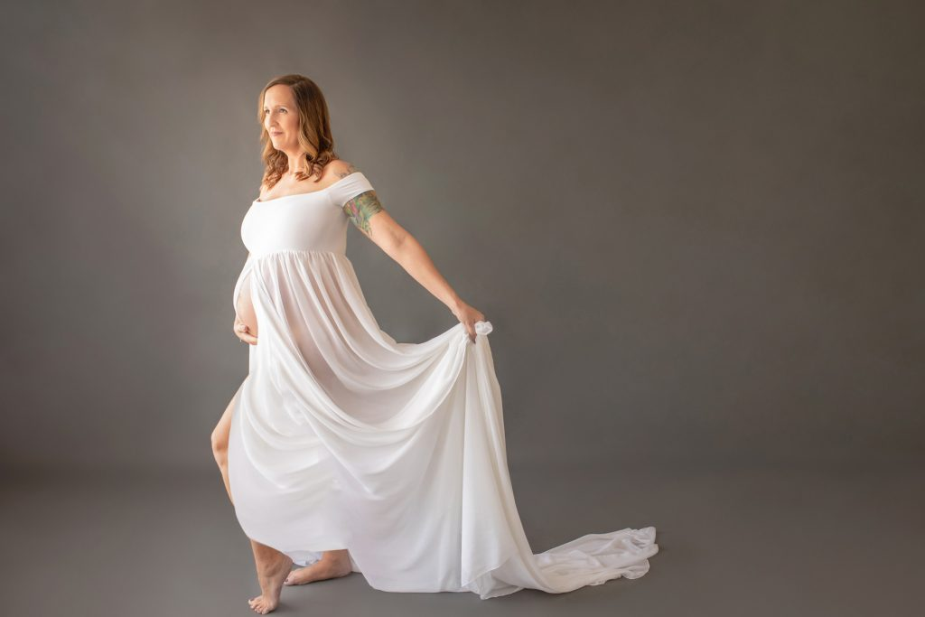 Beautiful pregnant mom in white chiffon maternity gown opened for belly to poke through with look of anticipation on grey background
