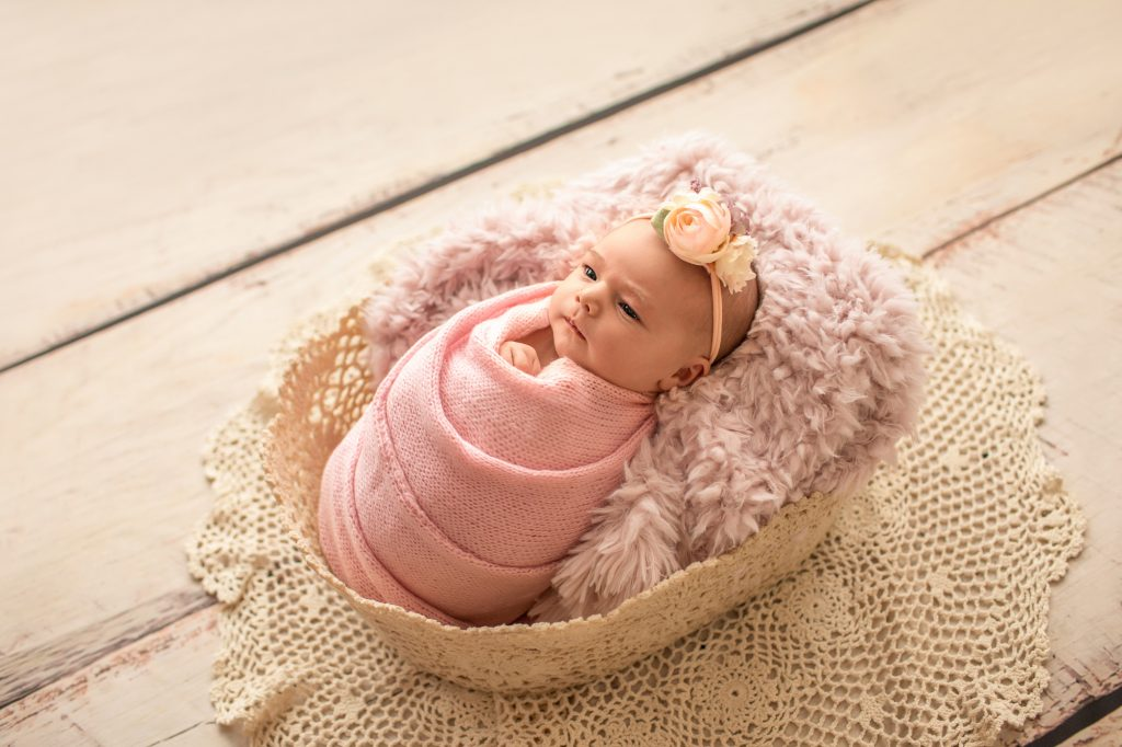 Gainesville Newborn moments newborn baby girl swaddled in pink knit wrap and floral headband posed in pink fur stuffed lace basket with lace accents Gainesville Florida newborn photography