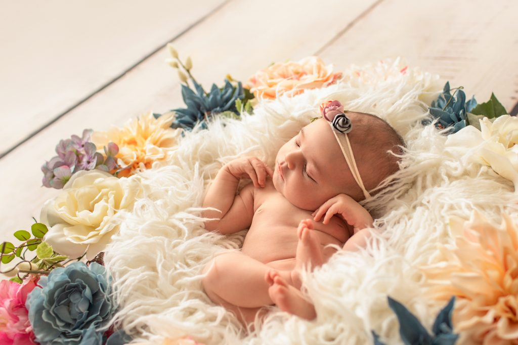 Gainesville Newborn moments newborn baby girl posed naked with delicate floral headband against white fur surrounded by dusty blue pink and ivory flowers photo with backlight Gainesville Florida newborn photography