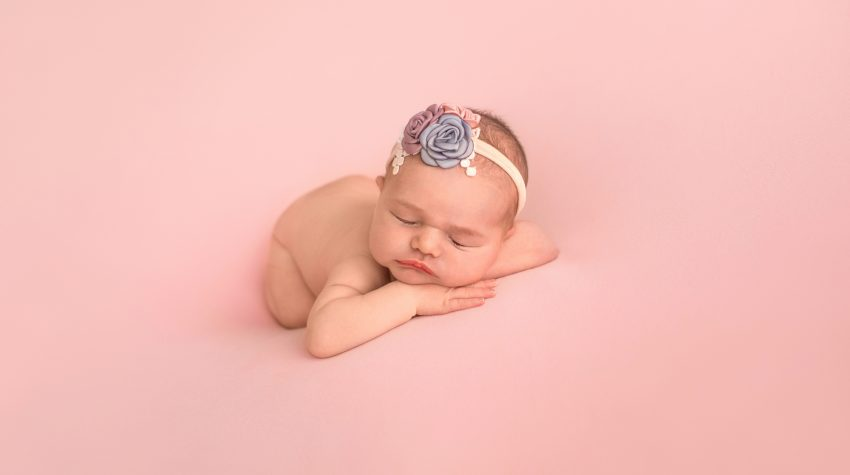 Gainesville Newborn moments baby girl posed naked with dusty blue pink lavender floral headband newborn baby posed on belly with bottom up resting chin upright on her hands lying on dusty pink blanket Gainesville Florida newborn photography