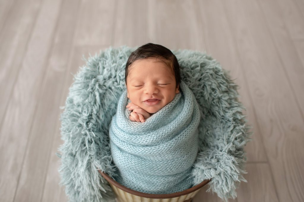 newborn photoshoot Christian smiles big from ear to ear in aqua knit blanket wrapped like potato sack with newborn hands folded below chin posed in aqua fur stuffed bucket on grey wood floor Gainesville FL newborn photography