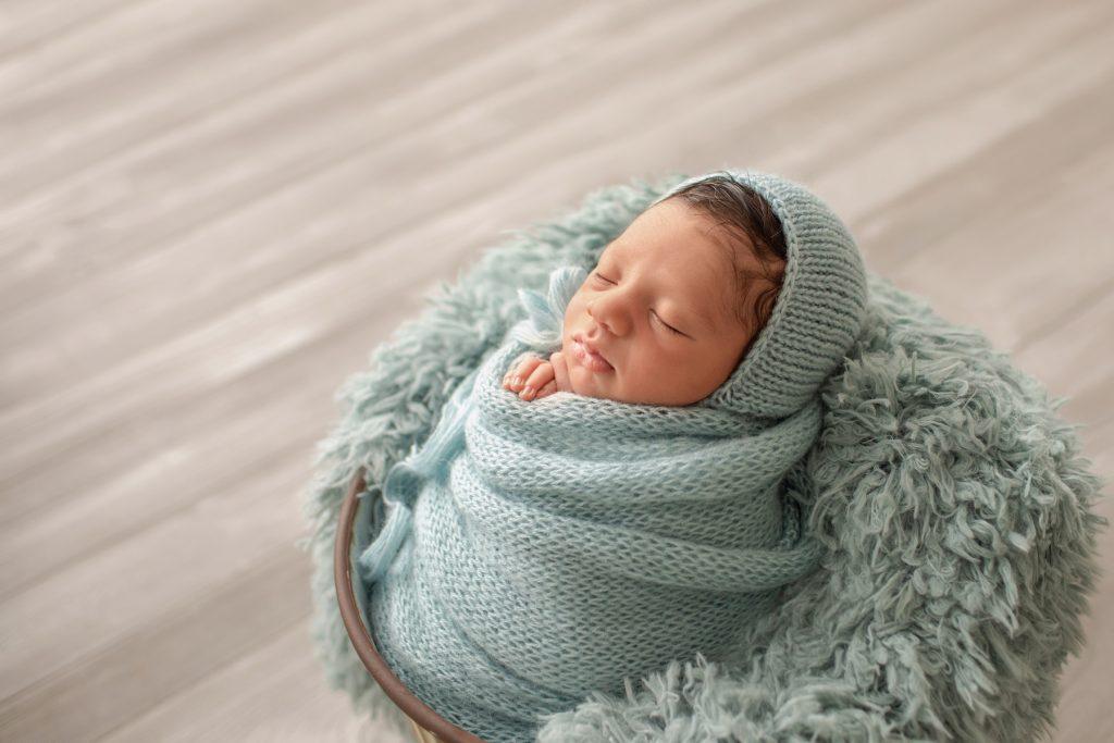 newborn boy Christian in aqua knit blanket wrapped like potato sack with newborn hands folded below chin matching aqua knit bonnet posed in aqua fur stuffed bucket on grey wood floor photo from side
