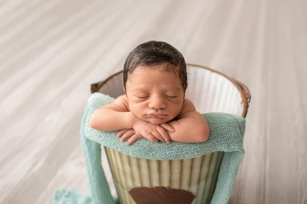 newborn boy Christian posed naked baby in a metal bucket with aqua on grey floor Gainesville Fl newborn picture