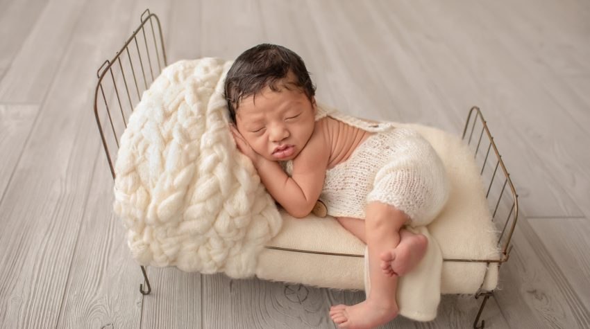 newborn wears cream knit romper with buttons posed with hand under cheek on cream covered metal bed with leg hanging off side of bed