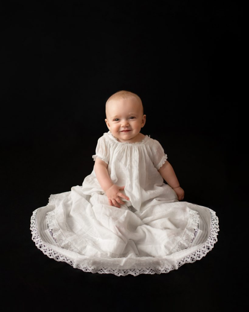 6 month old baby Rachel smiling posed in 205 year old baby christening gown sitting up against a solid black backdrop