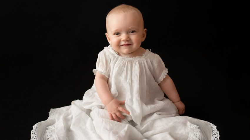 6 month old Rachel family heirloom photos smiling posed in 205 year old baby christening gown sitting up against a solid black backdrop