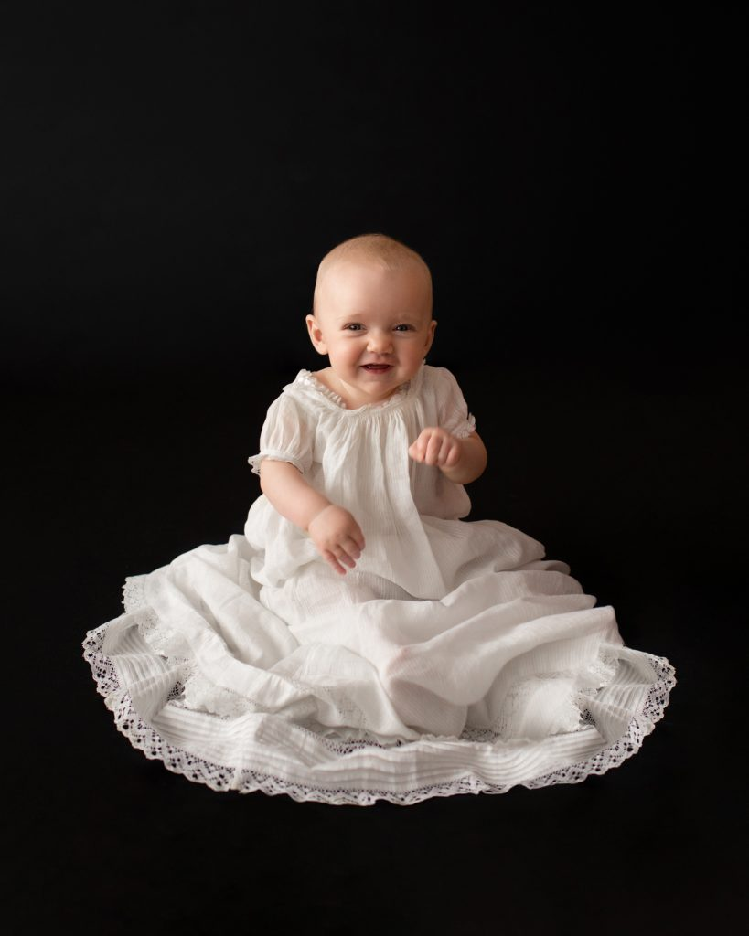 6 month old baby Rachel laughing posed in 205 year old baby christening gown sitting up against a solid black backdrop