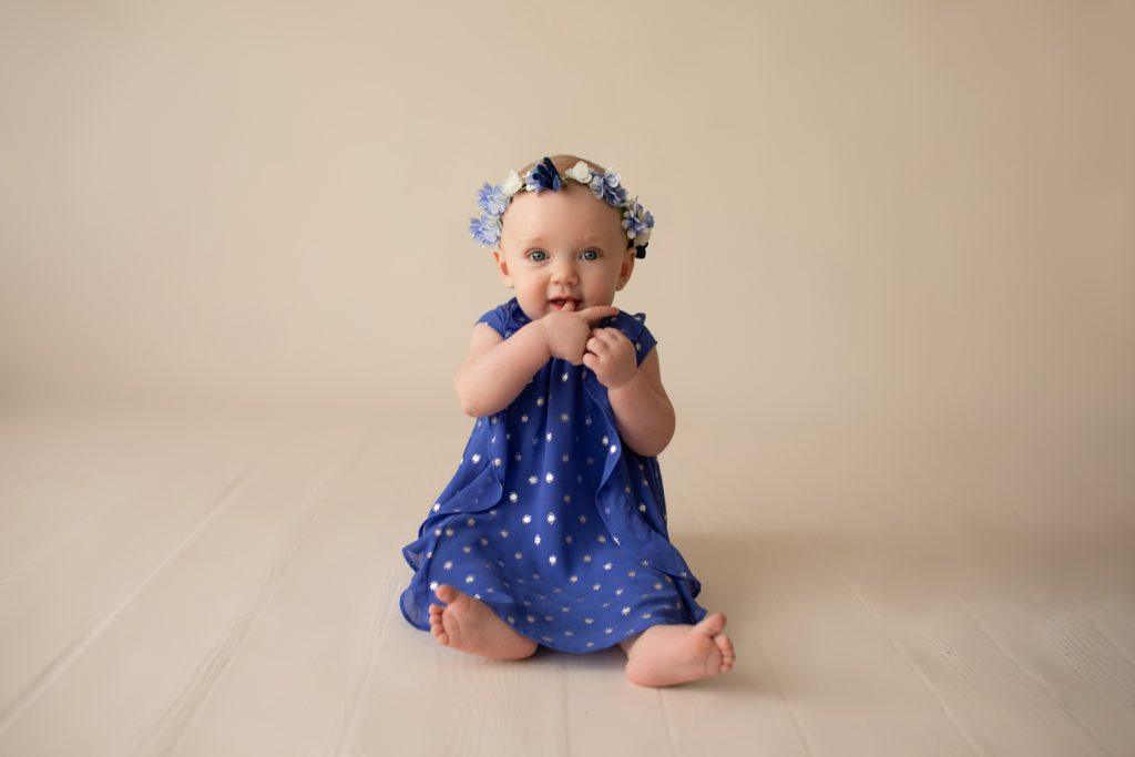 beautiful baby photos 6 month girl wears blue polka dot dress and floral crown hands in mouth