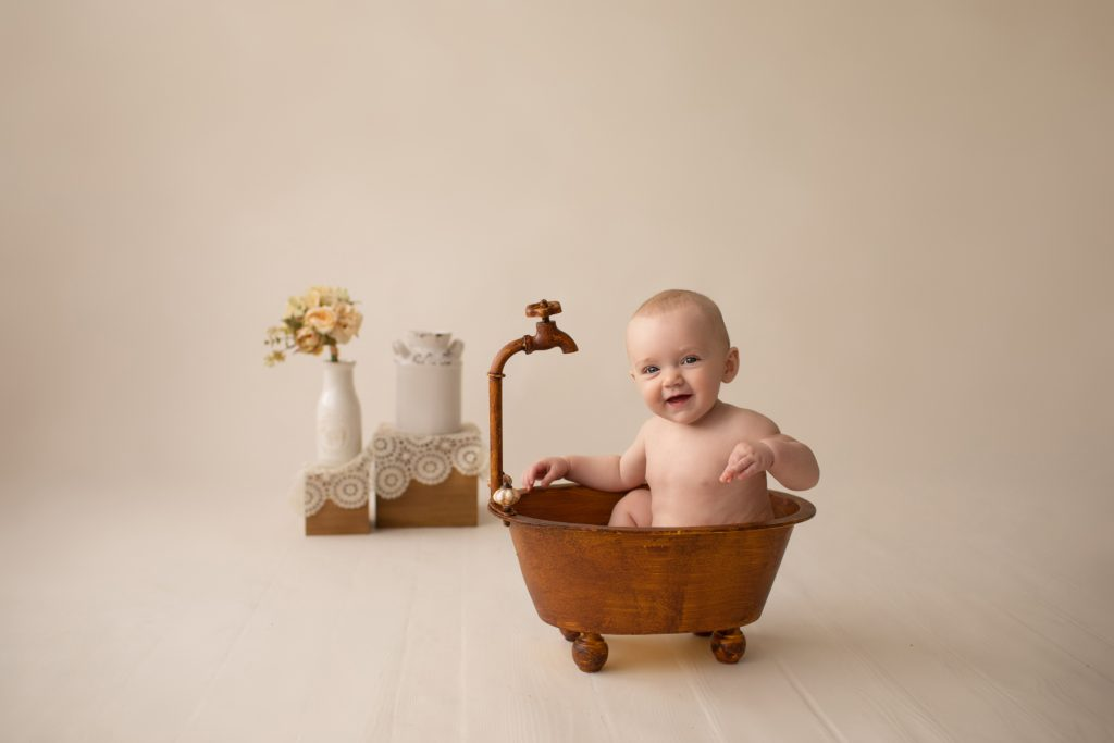 six month naked baby Rachel smiles with personality sitting in brown old fashioned tub playing peek