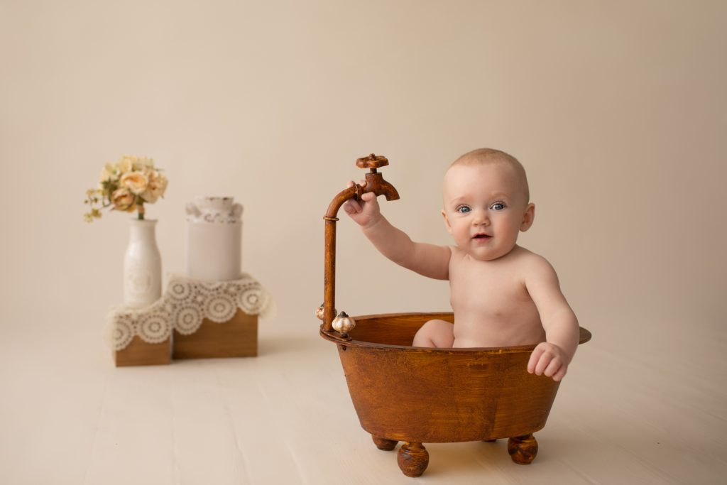 six month naked baby Rachel smiles with personality sitting in brown old fashioned tub