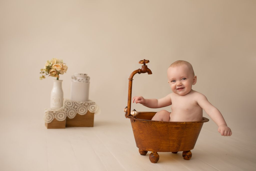 six month naked baby Rachel smiles with personality sitting in brown old fashioned tub with big smiles