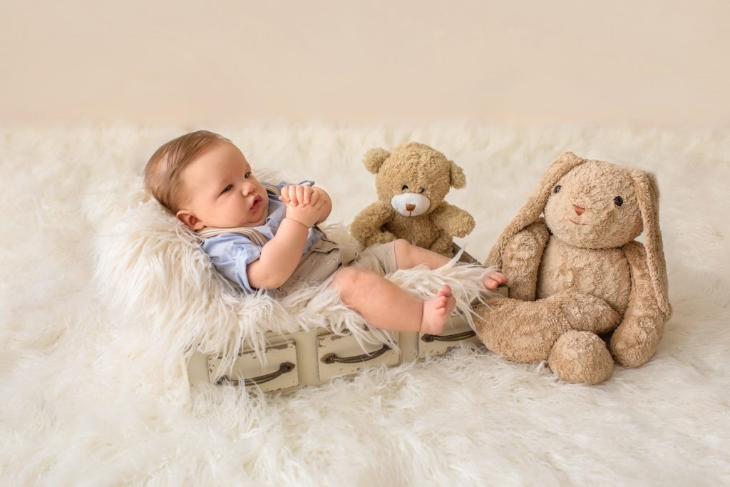 Baby in khaki shorts button up collared shirt suspenders with favorite teddy bear looking at mom