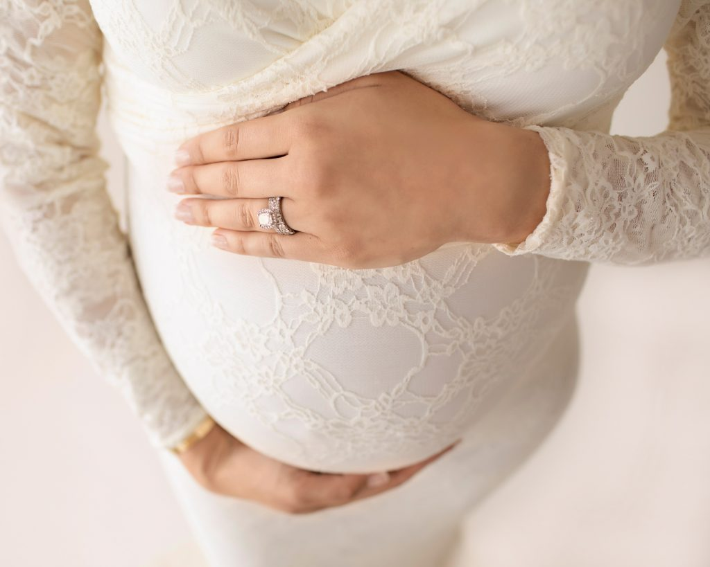 Gorgeous pregnant mom dressed in long sleeved ivory lace mermaid maternity gown holding beautiful baby belly with both hands