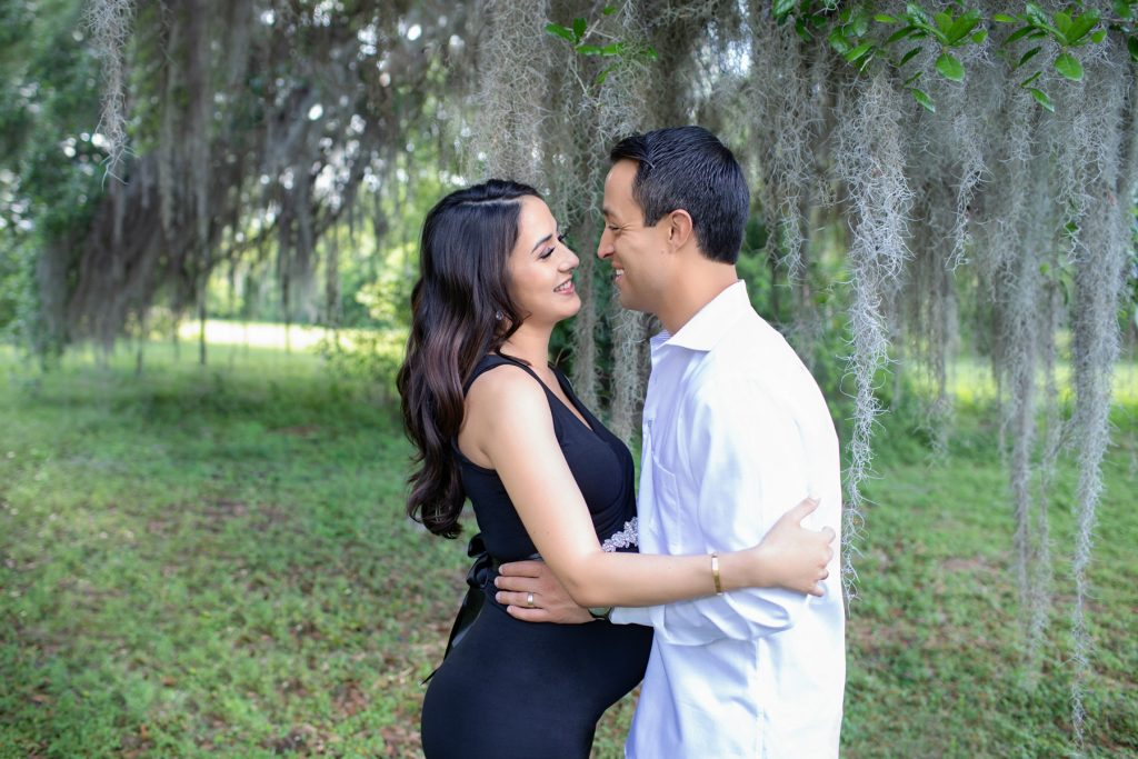 Beautiful pregnant mom dressed in black sleeveless v-neck maternity gown laughing posed profile facing dad at lush green park