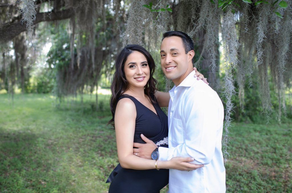 Beautiful pregnant mom dressed in black sleeveless v-neck maternity gown posed profile facing dad at lush green park