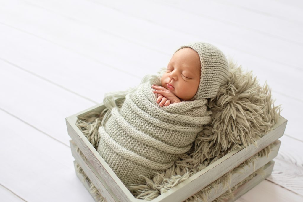 Baby boy snuggled with sage green knit wrap and bonnet on sage fur in crate