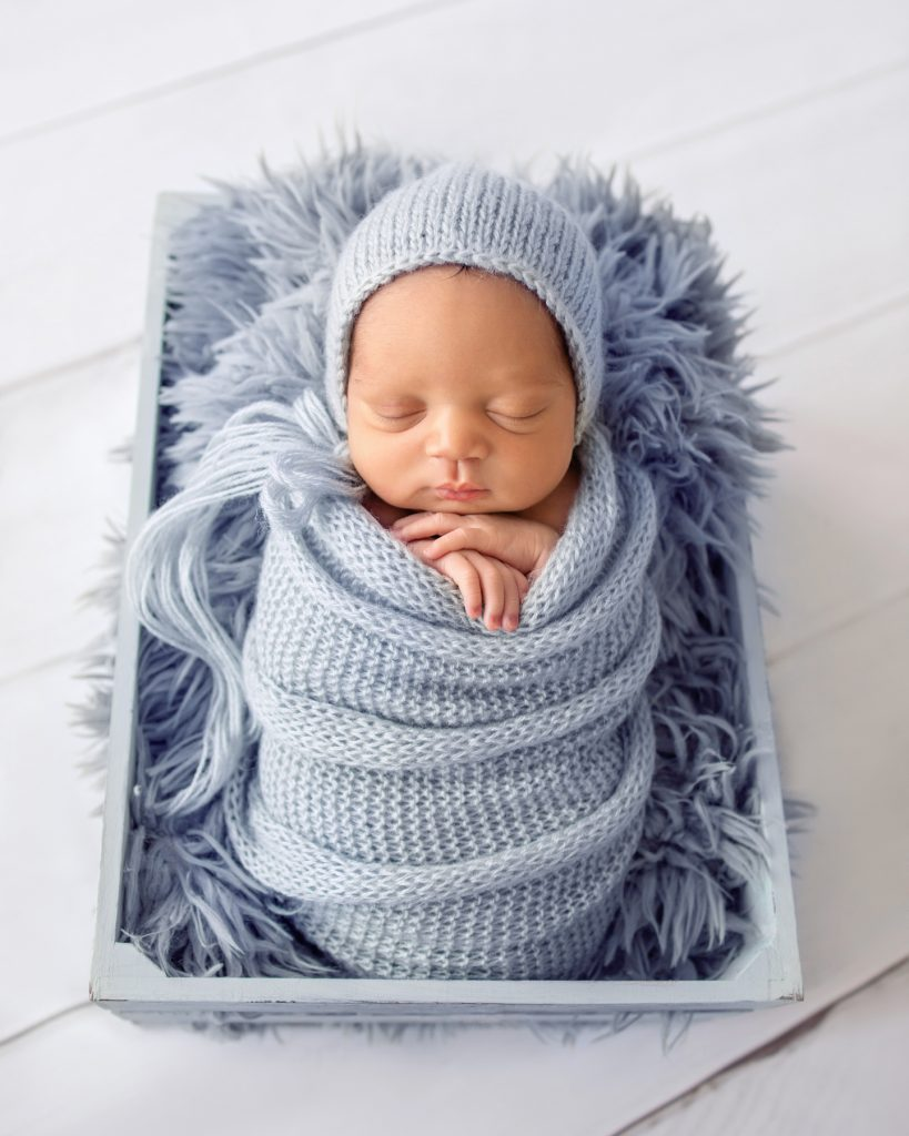 Baby boy chubby cheeks folded baby hands snuggled with light blue knit wrap and bonnet on blue fur in crate