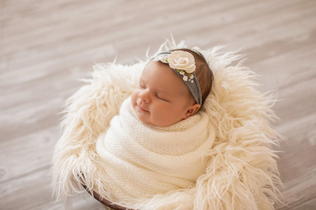 tiny baby girl Bryce swaddlied in white hand knitted blanket posed like a little potato sack in a bucket with white fur