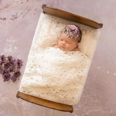 tiny baby girl Bryce sleeps under white lace blanket in baby bed with purple flowers and matching headband